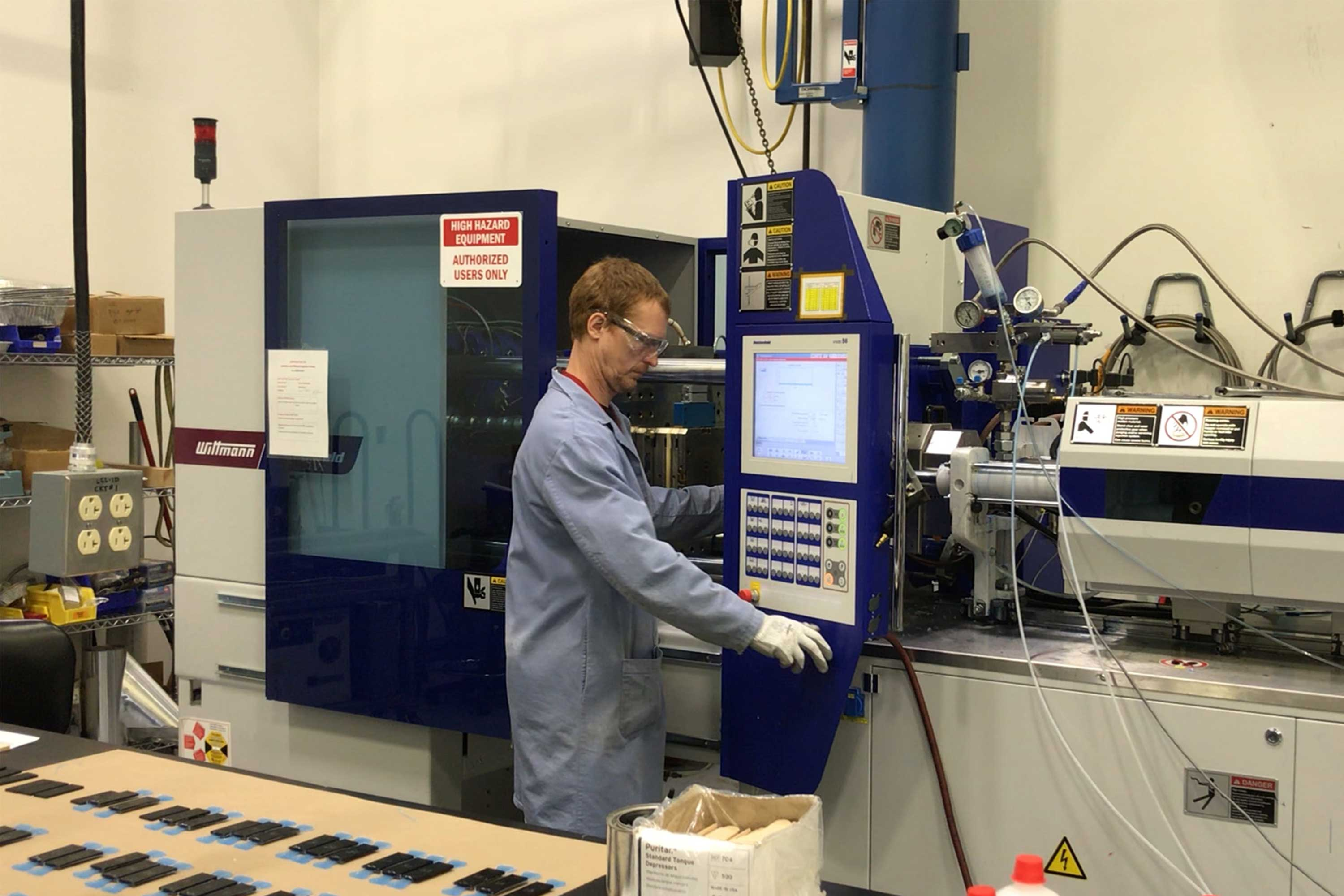 person looking at injection molding machine