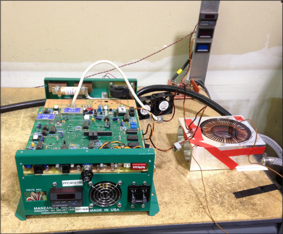Figure 4: Test set-up for one inductor potted with Thermoset SC-400 encapsulant showing the PFC40X-188 charger on the left, the potted inductor on the right, and the coolant inlet and outlet lines at the far right.
