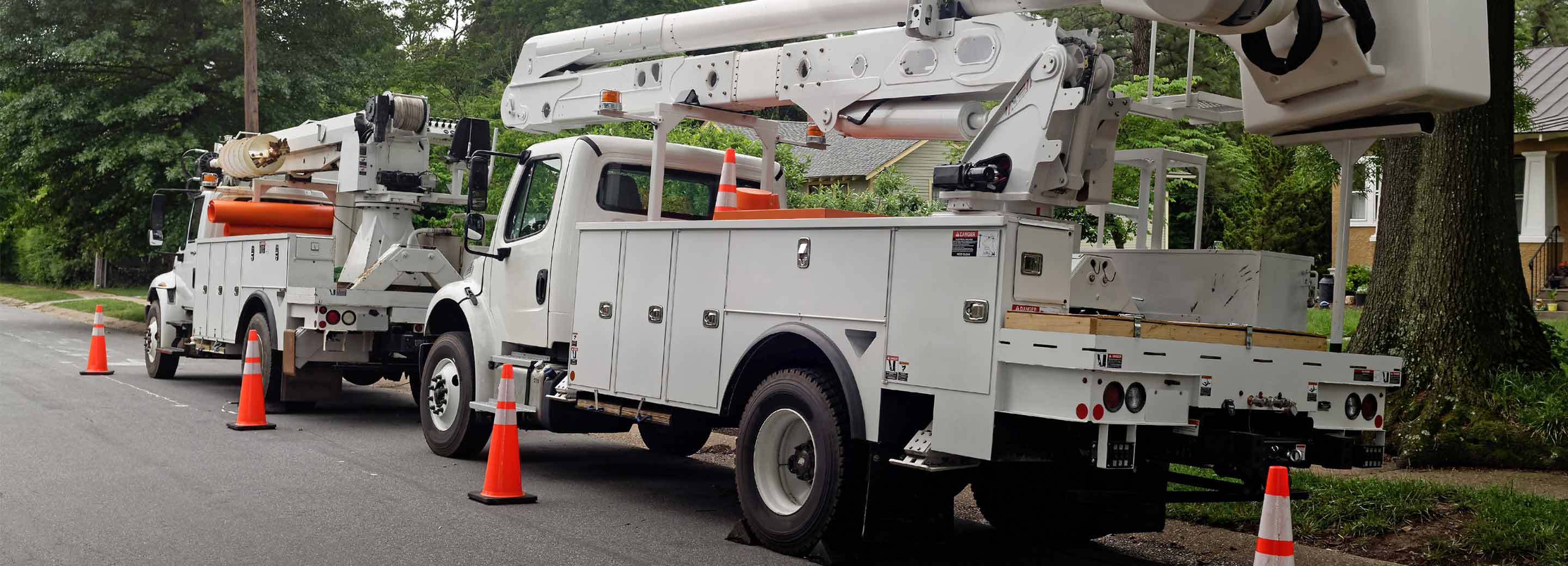 white boom truck with traffic cones