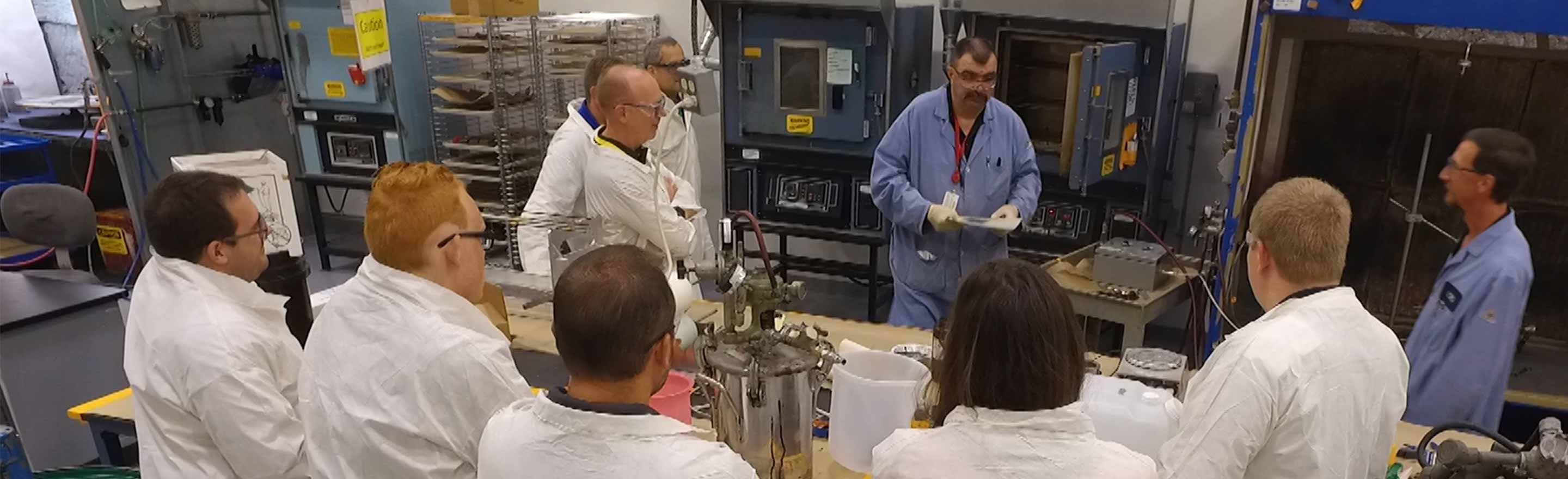 LORD academy training with attendees in lab coats watching demonstrations in the lab.