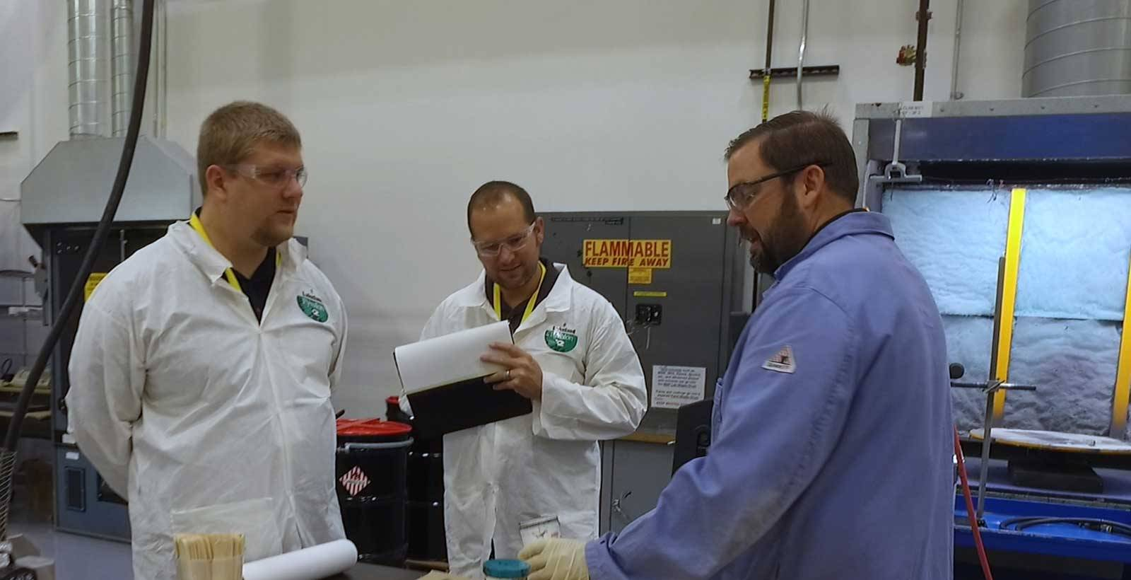 Scientist talking to two people in the lab learning about Chemlok Adhesives